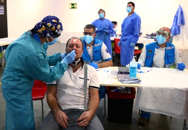 Un hombre se somete a un test de antígenos en un centro cultural habilitado para ello en el barrio...