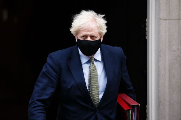 British Prime Minister Boris Johnson leaves 10 Downing Street wearing a face mask on his way to Prime...