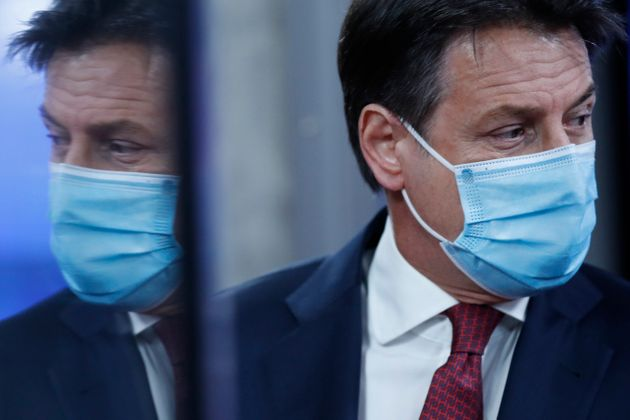 Italy's Prime Minister Giuseppe Conte wearing a mask is reflected in a glass door as he leaves during...