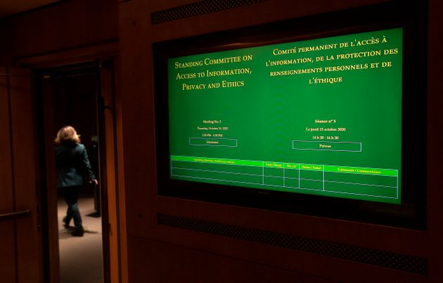 A woman walks inside the House of Commons on Thursday in Ottawa as a TV monitor shows the plans of the