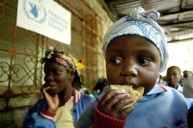 A Haitian child eats bread given by the World Food Program in the town of Chauffard, Haiti April 12,...