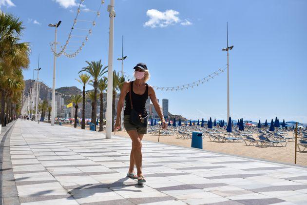 Una mujer camina por el paseo marítimo de Benidorm, con la playa completamente