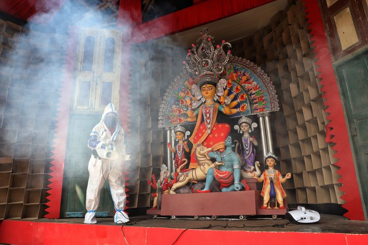 KOLKATA, WEST BENGAL, INDIA - 2020/10/13: A member of the Durga Puja committee dressed in a protective suit sprays disinfectants to sanitise a Pandal in front of an idol of Goddess Durga as a preventive measure against the spread of Coronavirus (COVID-19). (Photo by Jit Chattopadhyay/SOPA Images/LightRocket via Getty Images)