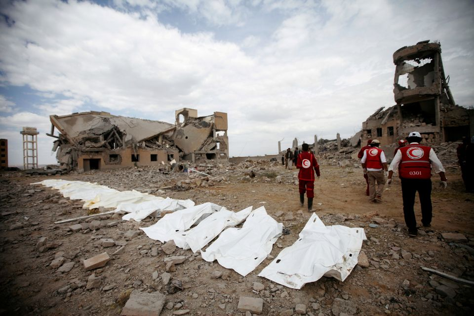Red Crescent medics walk next to bags containing the bodies of victims of Saudi-linked airstrikes on...