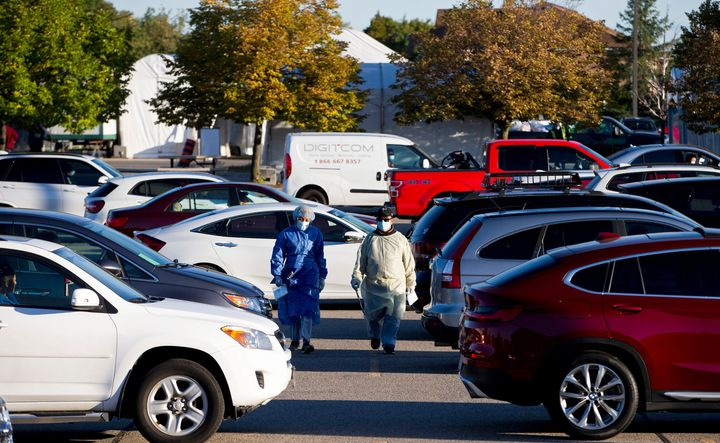 Two employees collect information from the people waiting in their cars at the Etobicoke General Hospital Drive-Thru coronavirus disease (COVID-19) testing facility in Etobicoke, Ont. on Sept. 18, 2020.