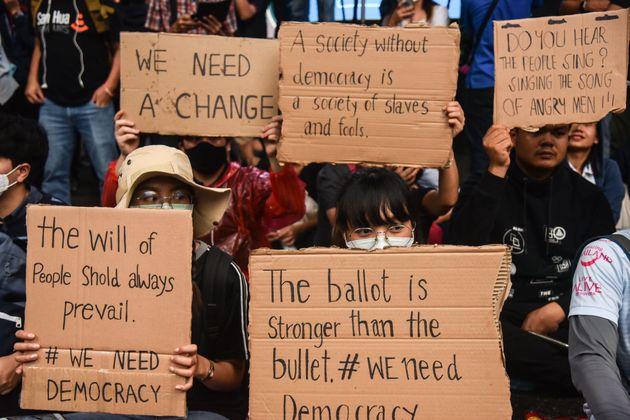 民主化を求めるメッセージが書かれたサインを掲げるデモ参加者(2020年10月16日)