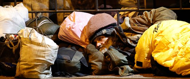 A homeless man rests in downtown Milan February 26, 2012. REUTERS/Max Rossi (ITALY - Tags: