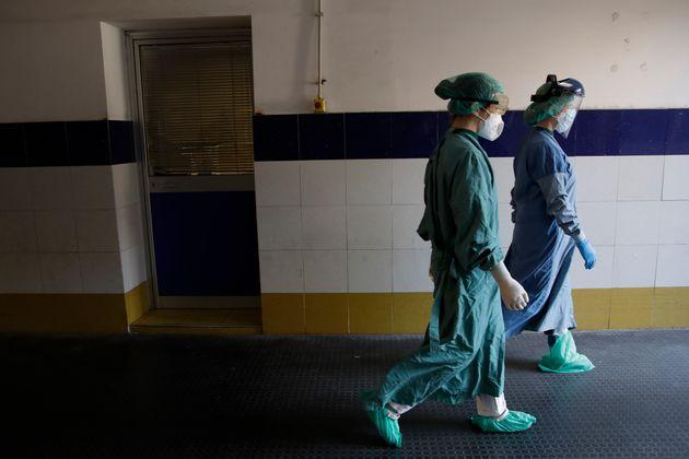 En esta imagen del domingo 12 de abril de 2020, trabajadoras médicas caminando por un pasillo hacia la...