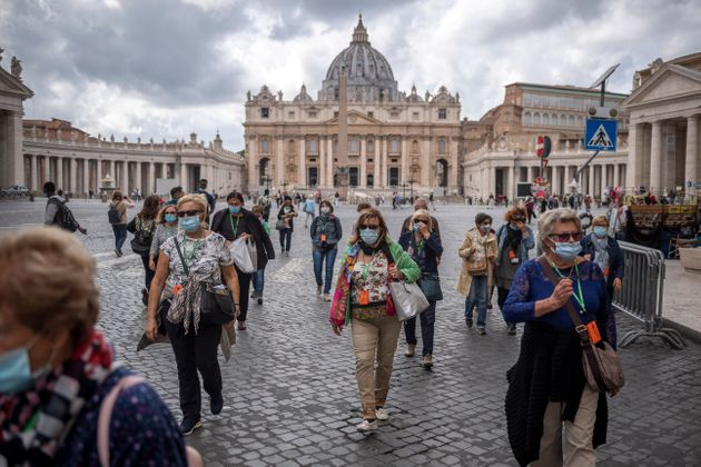ROME, ITALY - OCTOBER 02: Tourists wearing protective masks visit Piazza San Pietro (St. Peters Square)...