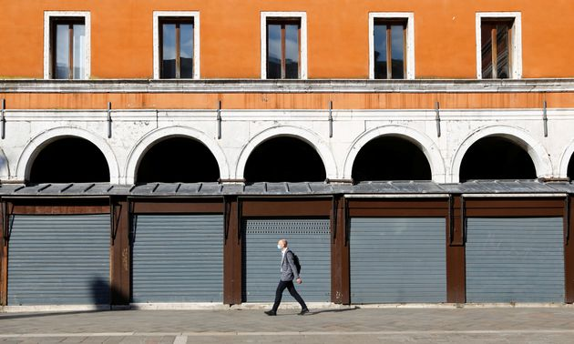 A man walks past closed shops at Rialto bridge, amid the coronavirus disease (COVID-19) outbreak, in...
