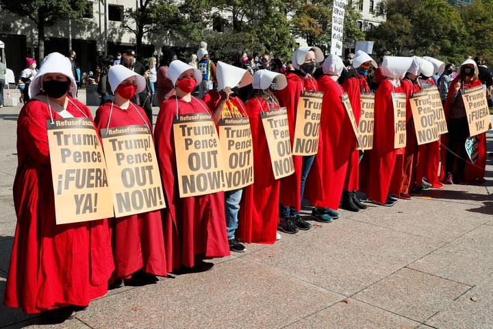 Women dressed as handmaidens protest against Donald Trump's presidency on Saturday.