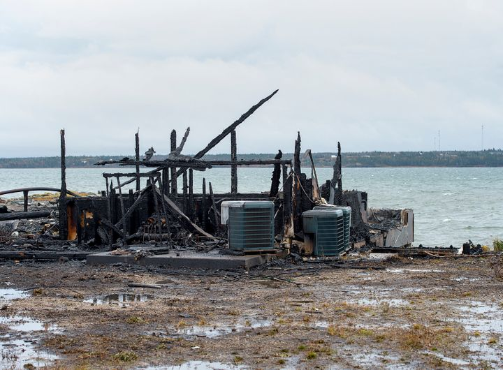 Debris from a burnt out fish plant is scattered along the shore in Middle West Pubnico, N.S. on Saturday.