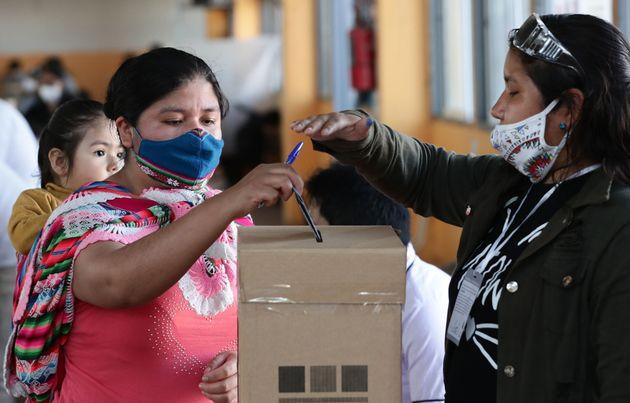 Uma residente boliviana (L) dá seu voto em uma seção eleitoral em Villa Celina,...