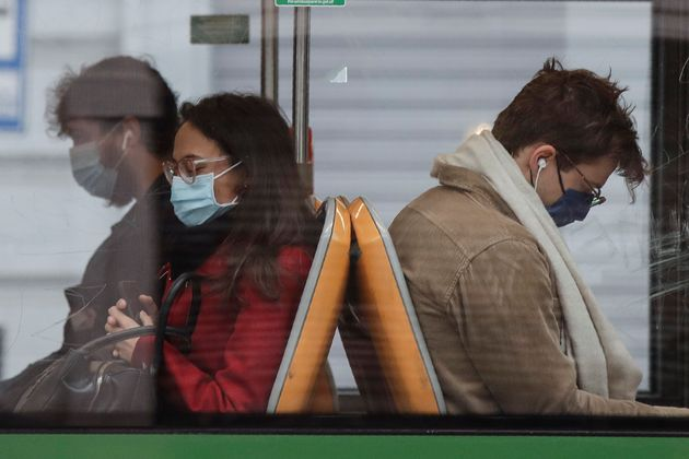 People wearing face masks to prevent the spread of COVID-19 sit on a bus, in Milan, Italy, Wednesday,...