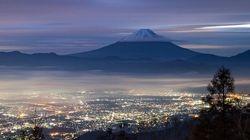 白い雪を被った富士山、姿を現す。街明かりで虹色に滲み、幻想的な雲海も