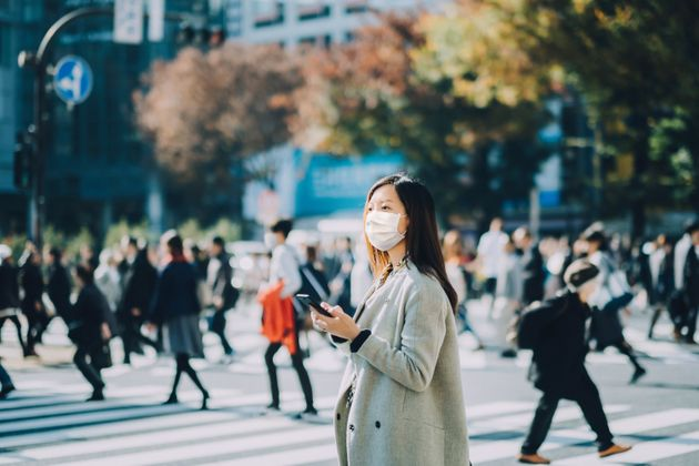 Young Asian businesswoman commuting in busy downtown city street with protective face mask and using...