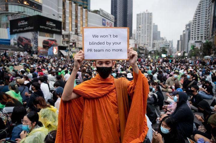 Un monje budista, partidario del movimiento a favor de la democracia, muestra una pancarta durante una manifestación de protesta en una intersección en Bangkok