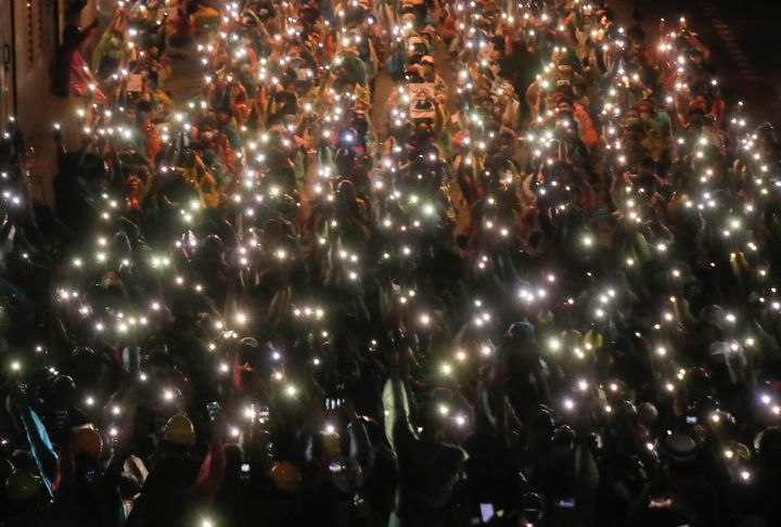 Pro-democracy protesters shine their mobile phone lights during an anti-government protest at Victory Monument during a prote