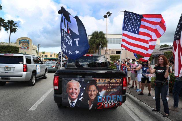 Una caravana de simpatizantes del Partido Demócrata pasa por delante de seguidores del presidente...