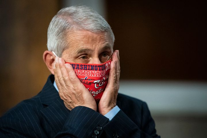 Dr. Anthony Fauci,director of the National Institute of Allergy and Infectious Diseases, adjusts his face mask as he ar