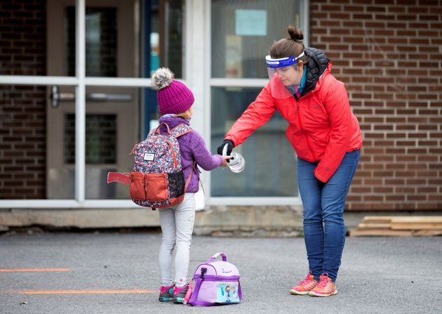 A student has her hands sanitized in the schoolyard in Saint-Jean-sur-Richelieu,