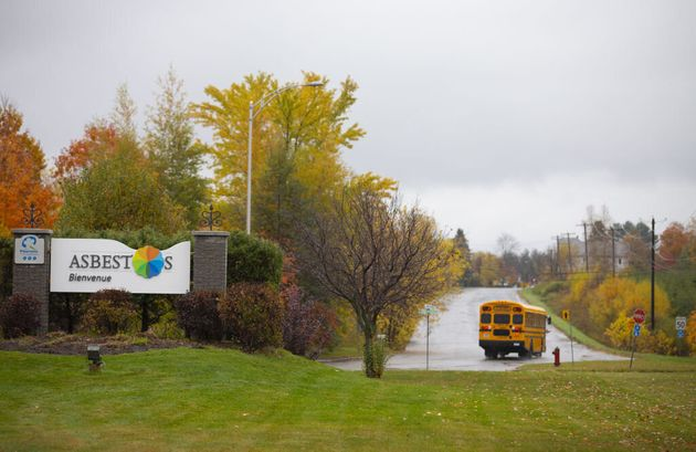 A school bus drives past a welcome sign on Oct. 16 in Asbestos, Que. The town is home to 7,000 people...