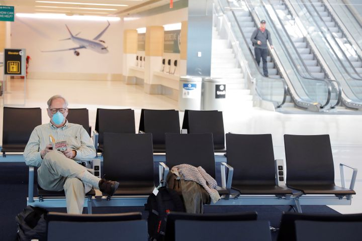 A traveler wears a mask while reading in John F. Kennedy International Airport in New York City. The CDC has advised that peo