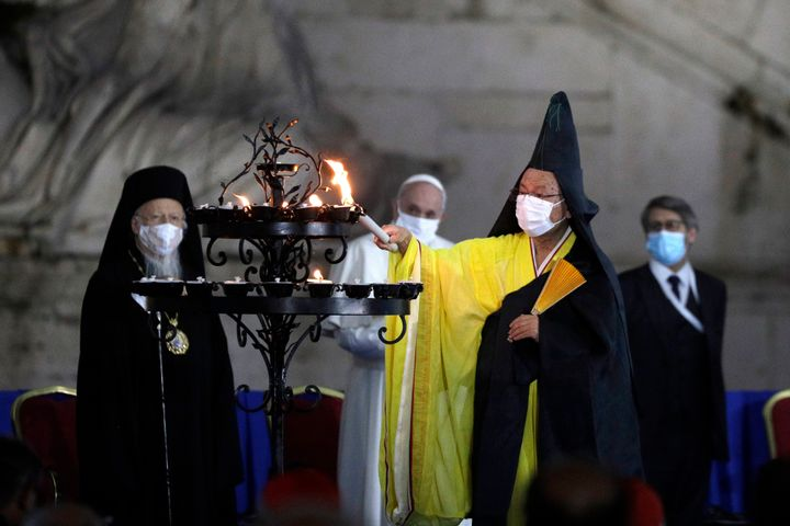 Buddhist monk Shoten Minegishi lights a candle for peace as Bartolomew I, Patriarch of Constantinopole, Pope Francis and Haim