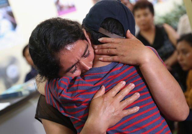 国境で引き離された息子とグアテマラで数カ月ぶりに再開。我が子を抱きしめる女性(2018年8月7日)