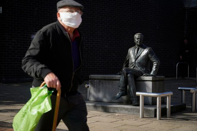 A man wearing a protective face mask walks past a statue of former prime minister Harold Wilson in Huyton...
