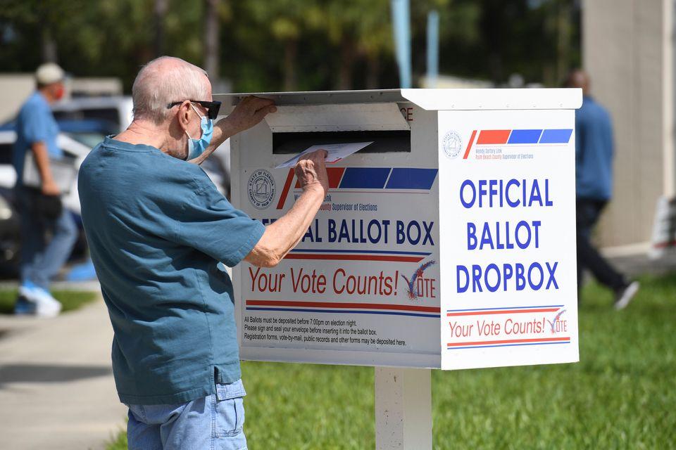 한 유권자가 공식 투표용지 수거함에 우편투표용지를 넣고 있다. 팜비치, 플로리다주. 2020년
