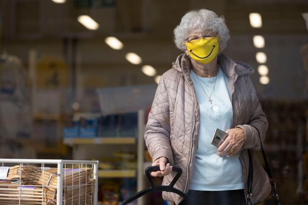 A woman smiles while wearing a novelty face mask in a shop on October 1, 2020 in Barry,