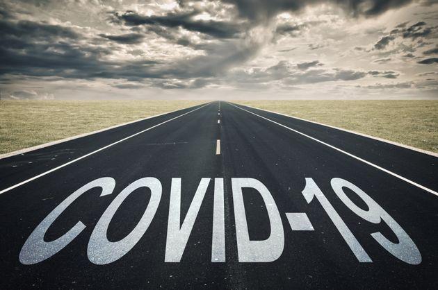 Covid-19 written on a road, dark clouds, coronavirus epidemic crisis
