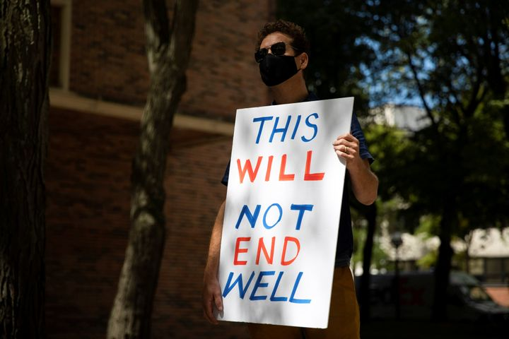 A faculty member holds a sign as students and faculty protest in-person classes for the fall semester at the University of Mi