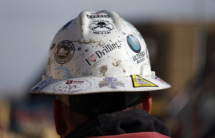A worker wears a protective helmet decorated with stickers during a hydraulic fracturing operation at an oil well near Mead,
