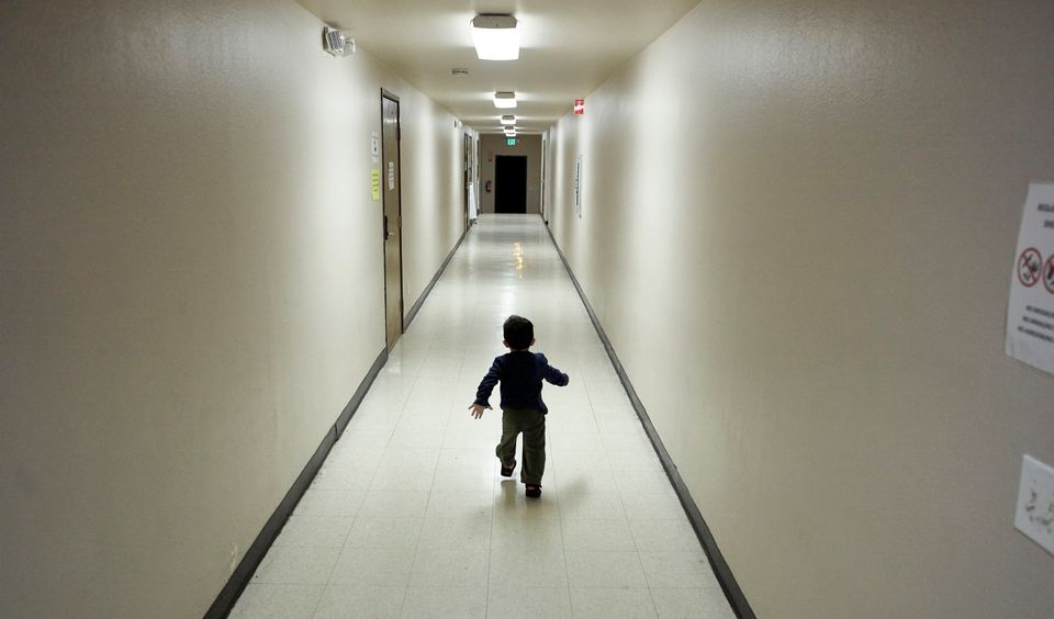 In this 2018 photo, an asylum-seeking boy from Central America runs down a hallway after arriving from...