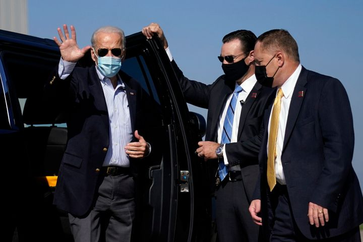 Joe Biden waves as he arrives to board his campaign plane at New Castle Airport in New Castle, Delaware, Thursday, Oct. 22, 2020, en route to Nashville.