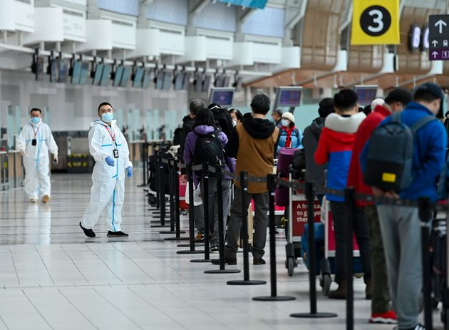 People line up and check in for an international flight at Pearson International airport during the COVID-19...
