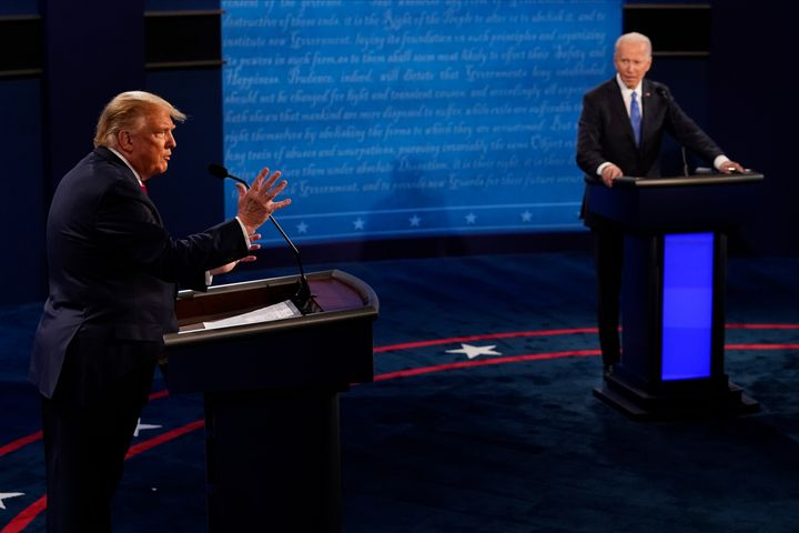 President Donald Trump answers a question as Democratic presidential candidate former Vice President Joe Biden listens during