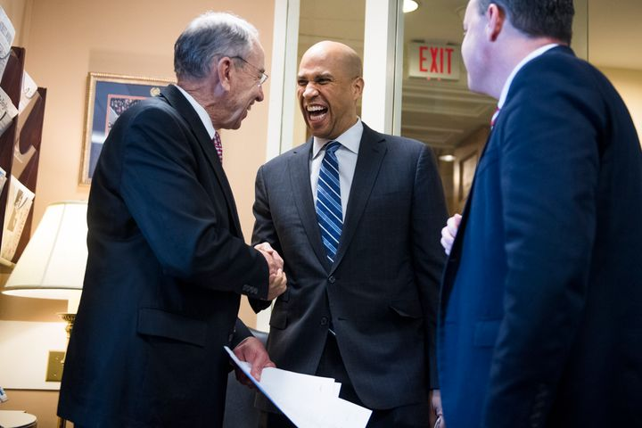 Sen. Cory Booker (D-N.J.) congratulates Republican Sens. Chuck Grassley (Iowa), left, and Mike Lee (Utah) on passage of the F