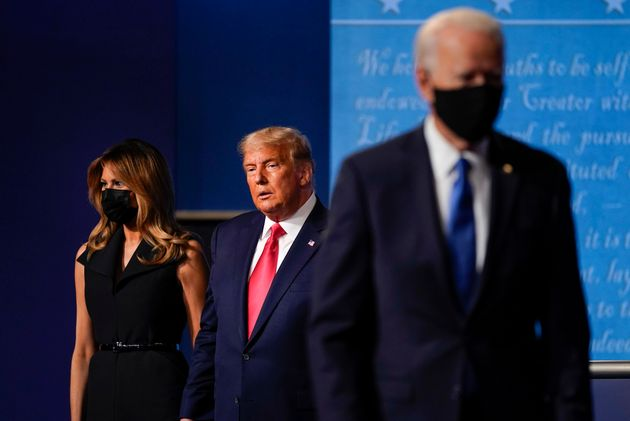 first lady Melania Trump, left, and President Donald Trump, center, remain on stage as Democratic presidential...