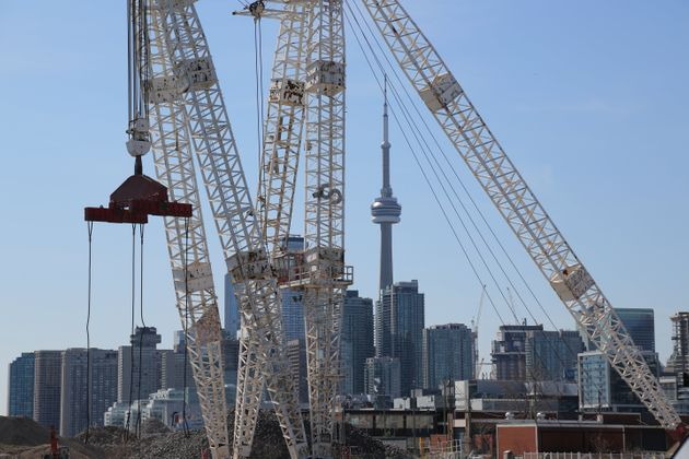 Toronto's downtown skyline and CN Tower are seen past cranes in the waterfront area, March 29, 2019....