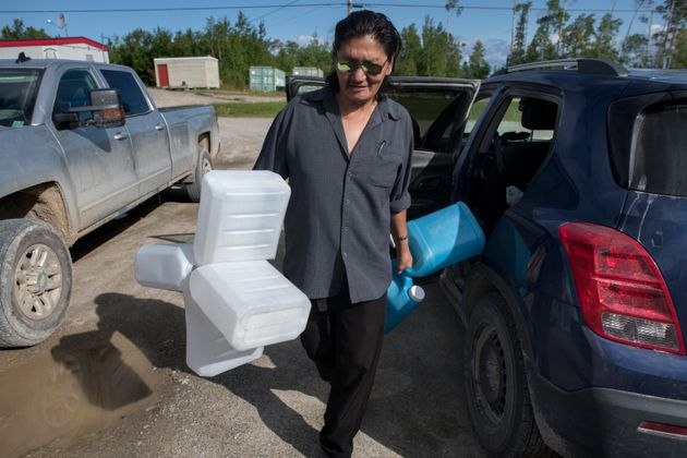 Norm Moonias carries nine jugs to fill with reverse osmosis water every three days in Neskantaga First...