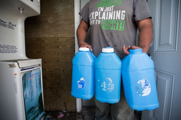 A resident of the Neskantaga First Nation carries jugs of water filled with reverse osmosis water in...
