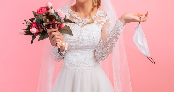 Bride in a wedding dress with a medical protective mask in her hands, on a pink background