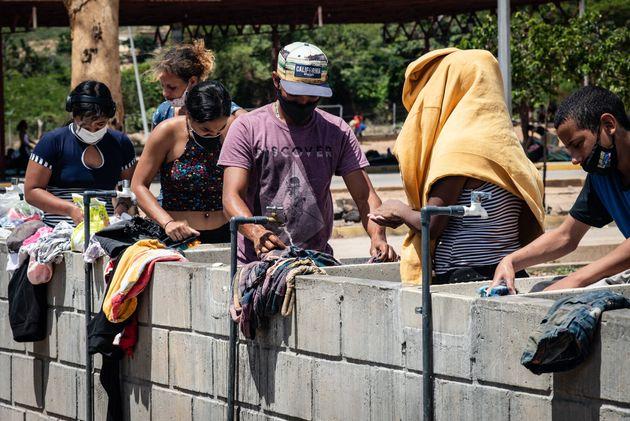 Migranti venezuelani lavano i loro vestiti in un centro quarantena nello stato di confine di