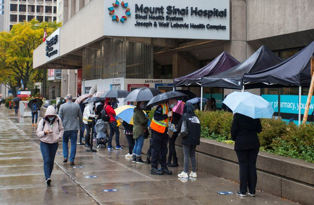 People line up for COVID-19 test outside an assessment centre in Toronto on Oct. 15,