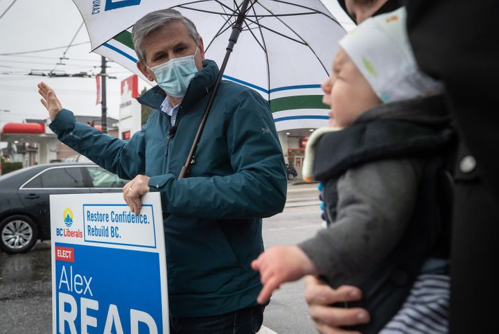 Liberal Leader Andrew Wilkinson waves to passing cars during a campaign stop in Vancouver on Oct. 23, 2020.