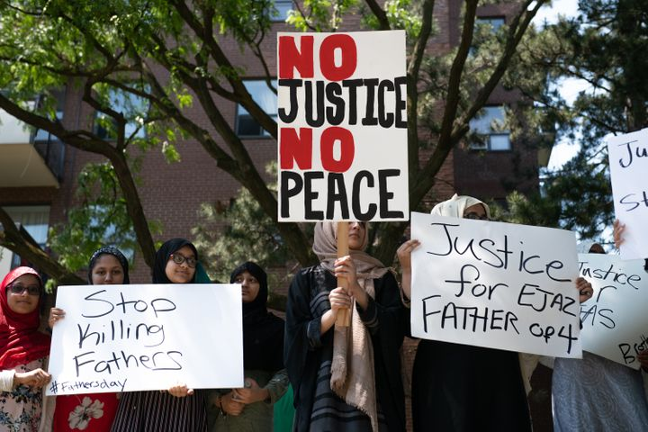 Protestors hold signs in front of the apartment building where Ejaz Choudry, a 62-year-old man who family members said was experiencing a schizophrenic episode, was shot by Peel Police and died at the scene the previous night, in Mississauga, Ont. on June 21, 2020.