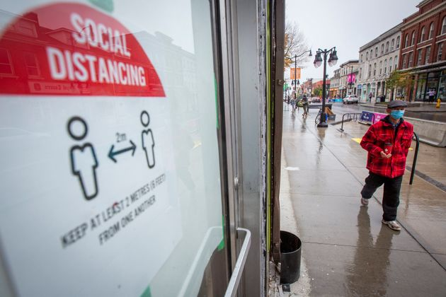 A person wears a mask as they walk by a sign telling people to social distance in Kingston, Ont. on